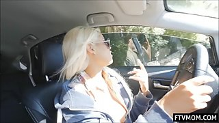 blonde milf with big tits drives a car